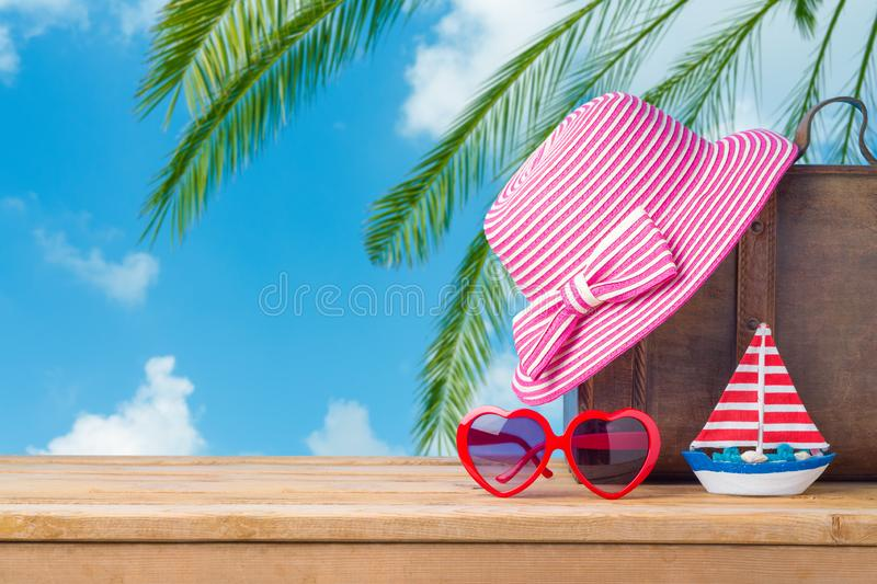 Summer vacation concept with suitcase, sunglasses, hat and boat over sea beach background stock images