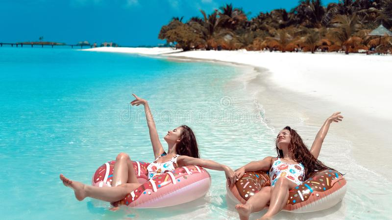 Summer Vacation. Enjoying suntan two women resting on donut float mattress in turquoise water on exotic beach. Maldives island. Paradise background. Beautiful royalty free stock photography