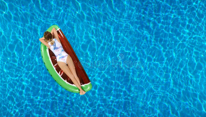 Woman in bikini on the inflatable mattress in the swimming pool. stock photography