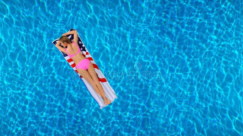 Woman in bikini on the inflatable mattress in the swimming pool. stock images
