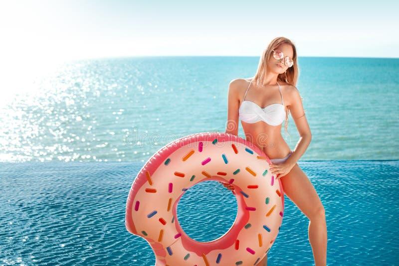 Summer Vacation. Enjoying suntan woman in white bikini with donut mattress near the ocean. Summer Vacation. Enjoying suntan woman in white bikini with donut royalty free stock photo