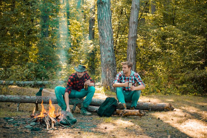 Summer vacation forest. Good day for spring picnic in nature. Spring or autumn camping. Friends men hikers watching fire. Together on camp. Happy young male royalty free stock photos