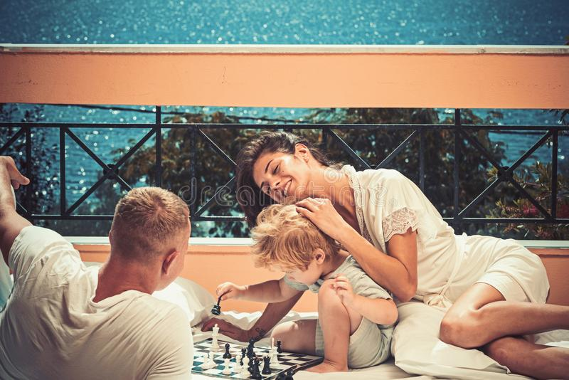Summer vacation of happy family. Child play chess with father and mother. Family travel with kid on mothers or fathers stock image