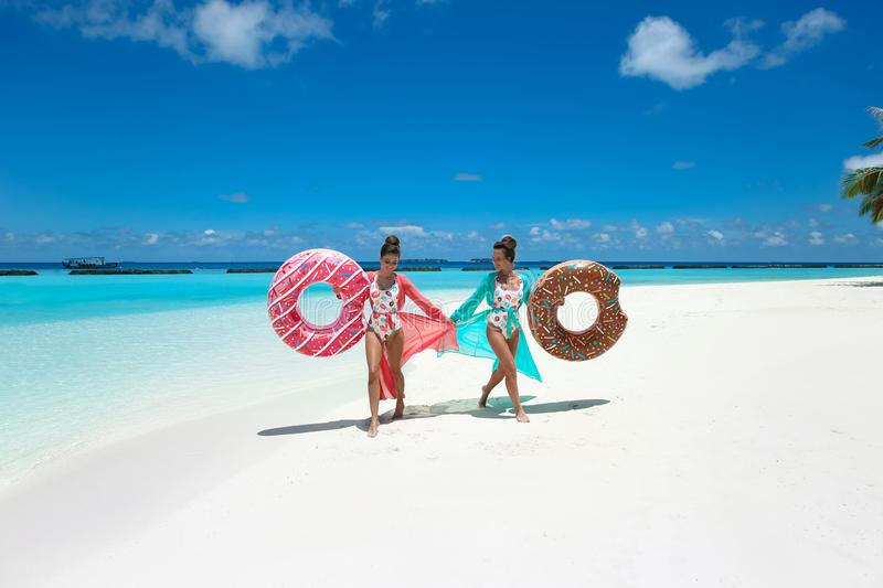 Summer Vacation. Happy free twoSummer Vacation. Happy free two women with donut float mattress. Girls wearing Chiffon Beach Dress royalty free stock image