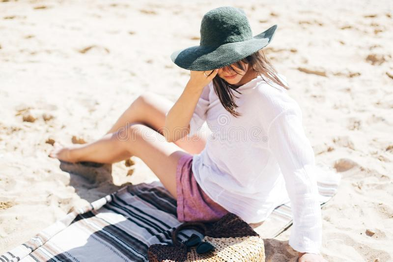 Summer vacation. Happy young boho woman relaxing and enjoying sunny warm day at ocean. Space for text. Stylish hipster girl in hat. Sitting on beach with straw royalty free stock photography