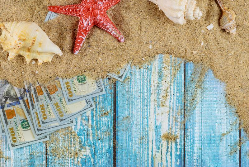 Summer vacation holiday concept starfish with sea shells in the beach sand over dollar bills. Summer vacation holiday concept starfish with sea shells in the stock photography