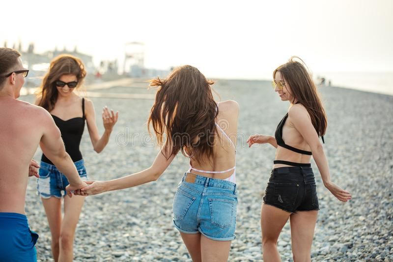 Women strolling along coastline. female friends walking together on beach, enjoying summer vacation royalty free stock images