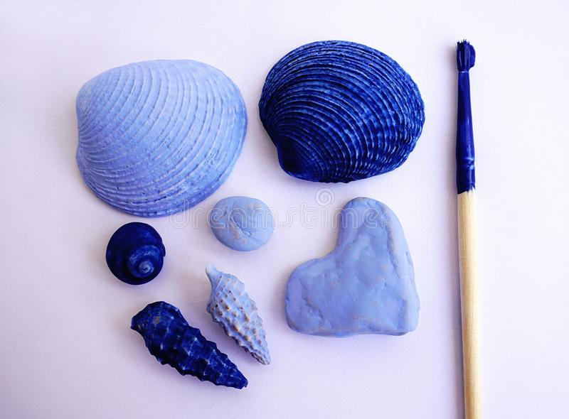 Summer vacation memories concept. Shells and pebbles painted in light and dark blue color and brush with blue color on it. Diy stu stock images