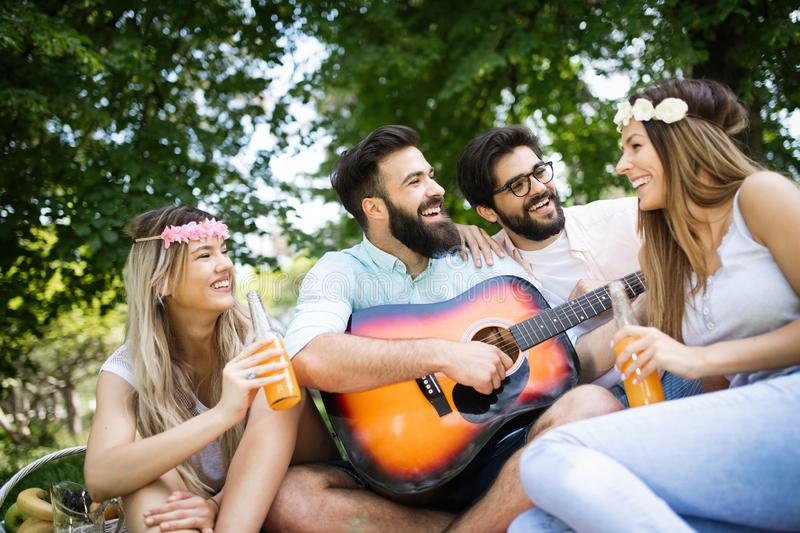 Summer, vacation, music and recreation time concept. Group of friends have picnic outdoor. royalty free stock image