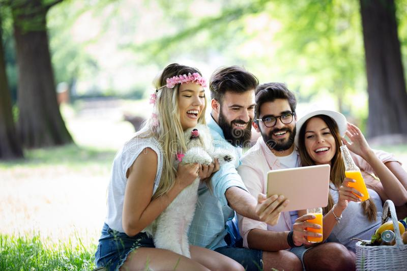 Summer, vacation, music and recreation time concept. Group of friends have picnic outdoor. stock photos
