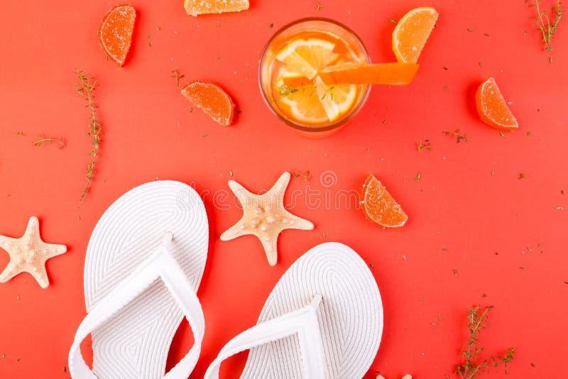 Summer vacation. Orange fruit cocktail, detox water near white flip flops. royalty free stock images