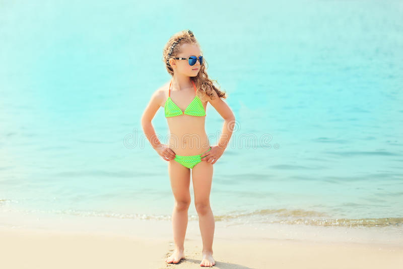 Summer vacation, relaxation, travel concept - little girl child on beach wearing sunglasses and swimsuit royalty free stock photography