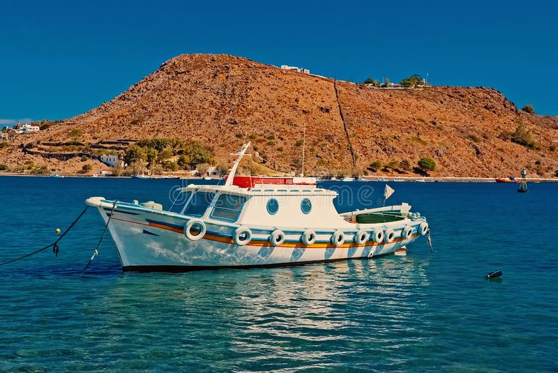 Summer vacation and sea travel. Boat in blue sea in Patmos, Greece. Small ship at seaside with mountain on sunny sky. Vessel and water transport. Wanderlust royalty free stock image
