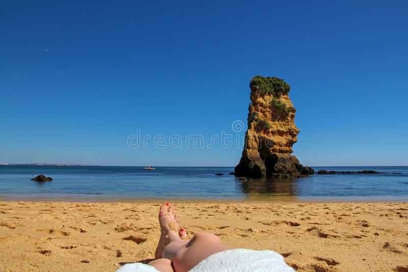Female suntanned legs, rock formation and turquoise in the background. Summer vacation selfie- female suntanned legs, rock formation and turquoise in the stock photo