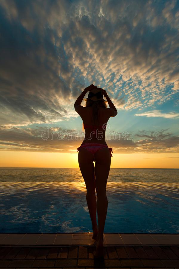 Summer Vacation. Silhouette of beauty dancing woman on sunset near the pool with ocean view. royalty free stock photography