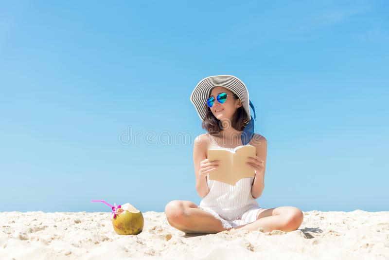 Summer Vacation. Smelling asian women relaxing and reading book on the beach, so happy and luxury in holiday summer, blue sky back. Summer Vacation. Smelling stock images