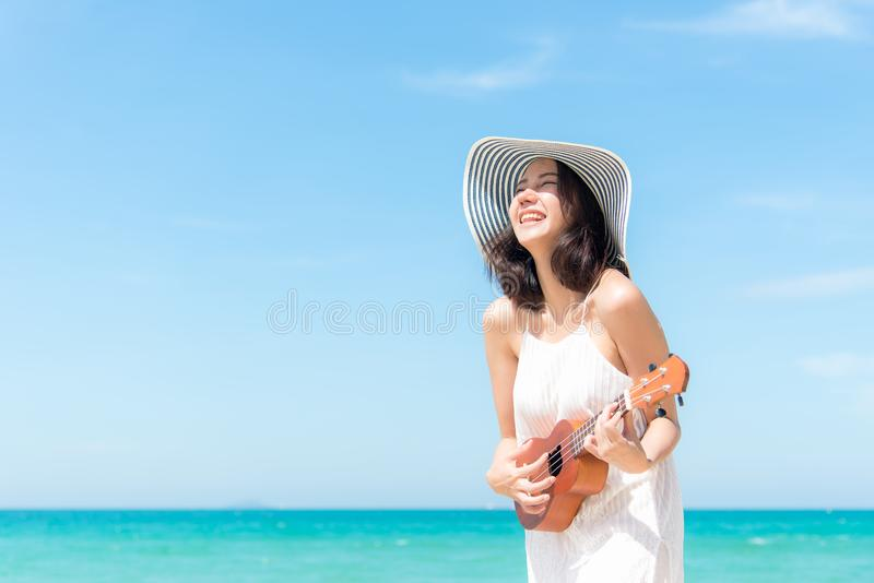 Summer Vacation. Smelling asian women relaxing and playing an ukulele on the beach, so happy and luxury in holiday summer, royalty free stock photo