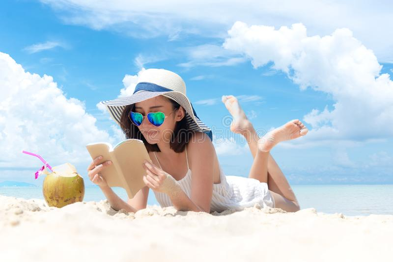 Summer Vacation. Smelling asian women relaxing and reading book on the beach, so happy and luxury in holiday summer, outdoors blue royalty free stock images
