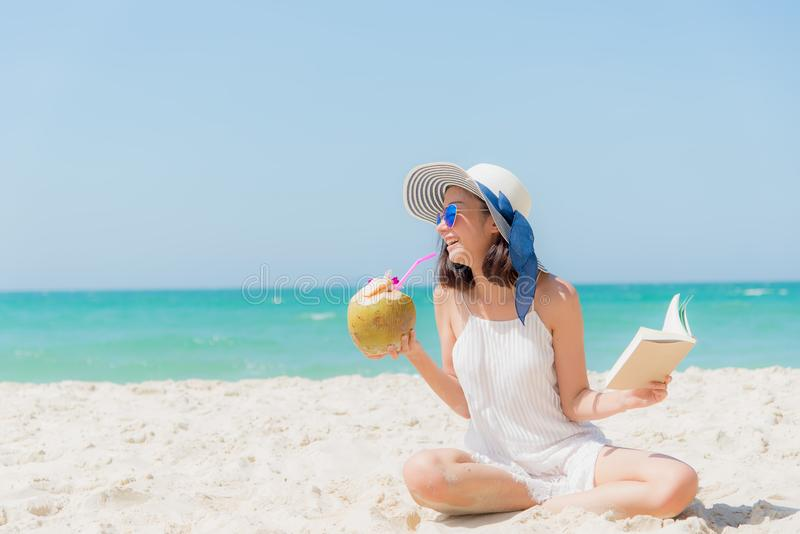 Summer Vacation. Smelling asian women relaxing, reading book and drinking coconut cocktail on the beach, royalty free stock photos