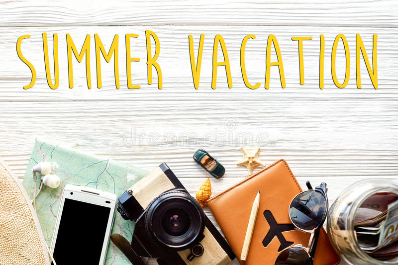 Summer vacation text, time to travel concept, wanderlust vacation background flat lay. camera sunglasses passport money map phone. Hat on white wooden table stock photography