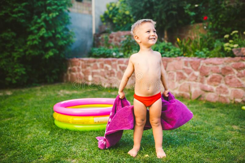 Summer vacation theme. A small 3 year old Caucasian boy playing in the backyard of a house on the grass near a round inflatable co. Lored pool wrapped up, wiped royalty free stock photos