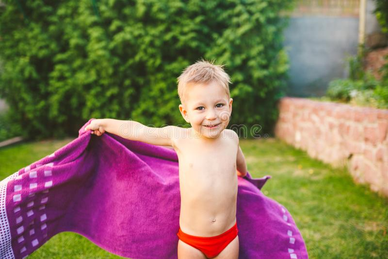 Summer vacation theme. A small 3 year old Caucasian boy playing in the backyard of a house on the grass near a round. Inflatable colored pool wrapped up, wiped stock photography