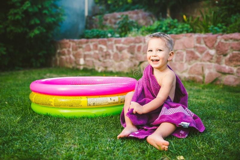Summer vacation theme. A small 3 year old Caucasian boy playing in the backyard of a house on the grass near a round inflatable co. Lored pool wrapped up, wiped royalty free stock images