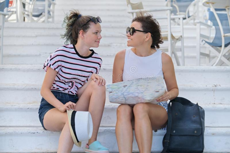 Summer vacation together mother and daughter traveling reading tourist map stock images