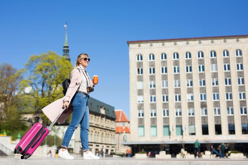 Summer vacation, tourism and travel concept - young woman with suitcase walking in old town stock image