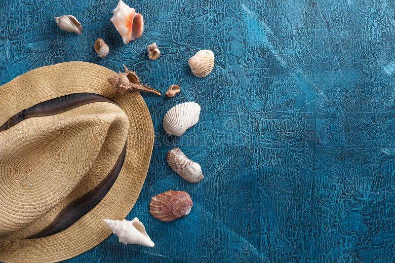 Summer vacation, tourism, travel, holiday concept. Sea shells, beach hat and blue colors on wooden background. Top view with space stock photo