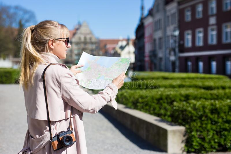 Summer vacation and travel concept - back view of woman in sunglasses with map and camera walking in old town royalty free stock image