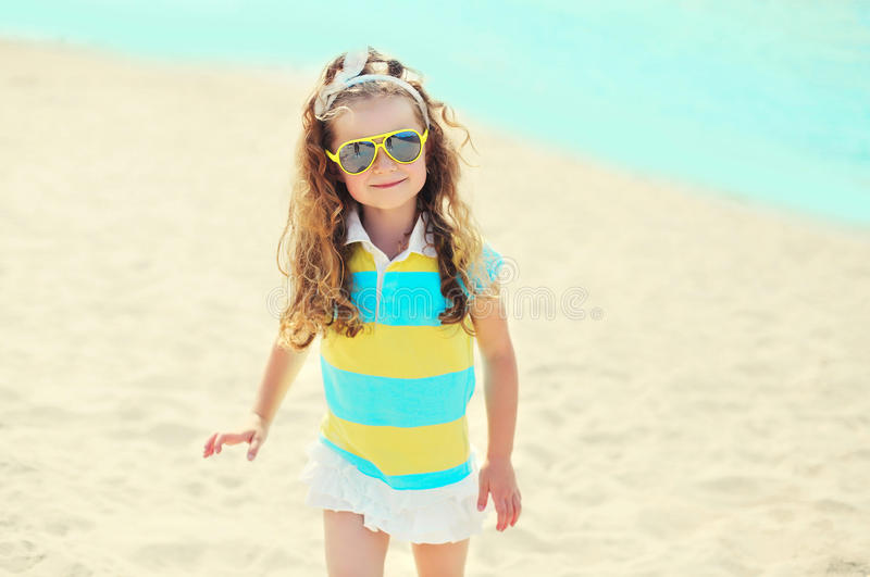 Summer vacation, travel concept - little girl child on beach wearing sunglasses stock photos