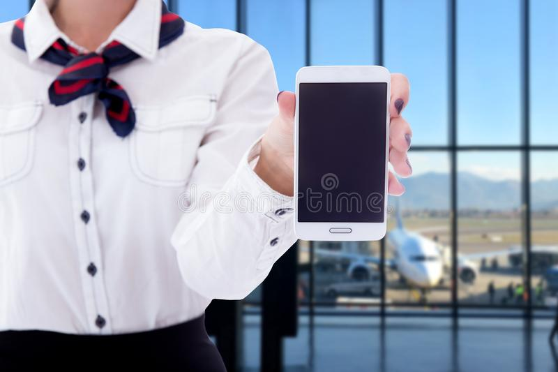 Summer, vacation and travel concept - smart phone with blank screen in stewardess hands stock images