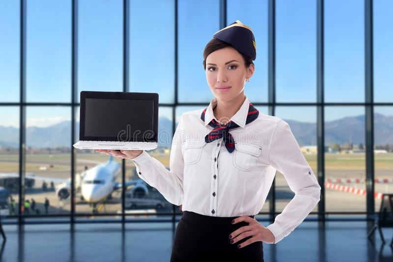Summer, vacation and travel concept - stewardess holding laptop with blank screen in airport royalty free stock photography