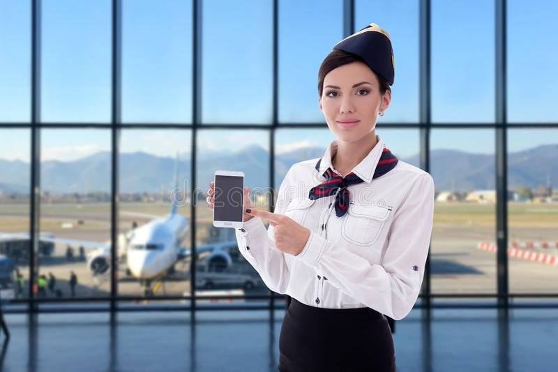 Summer, vacation and travel concept - stewardess holding smart phone with blank screen in airport stock photography