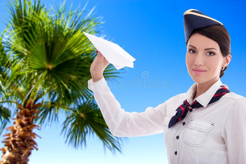 Summer, vacation and travel concept - stewardess with paper plane over blue sky background royalty free stock photo