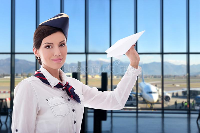 Summer, vacation and travel concept - young stewardess with paper plane in airport royalty free stock photos