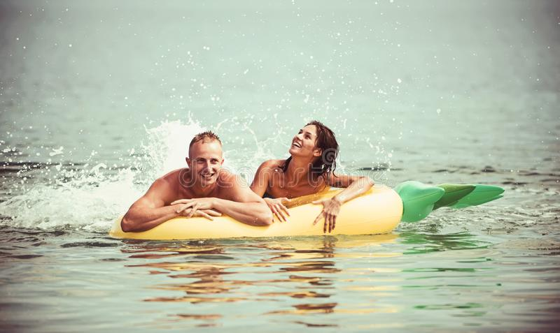 Summer vacation and travel to ocean. Couple in love sunbath on beach on air mattress. Pineapple inflatable mattress royalty free stock photos