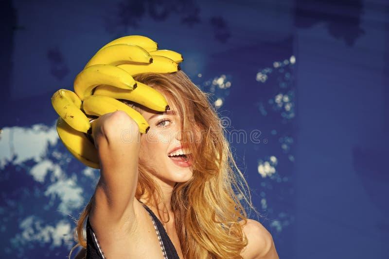 Summer vacation and travel to ocean. Vitamin in banana at girl near water. Dieting and healthy organic food, vegetarian. Sensual woman. Summer vacation and royalty free stock image