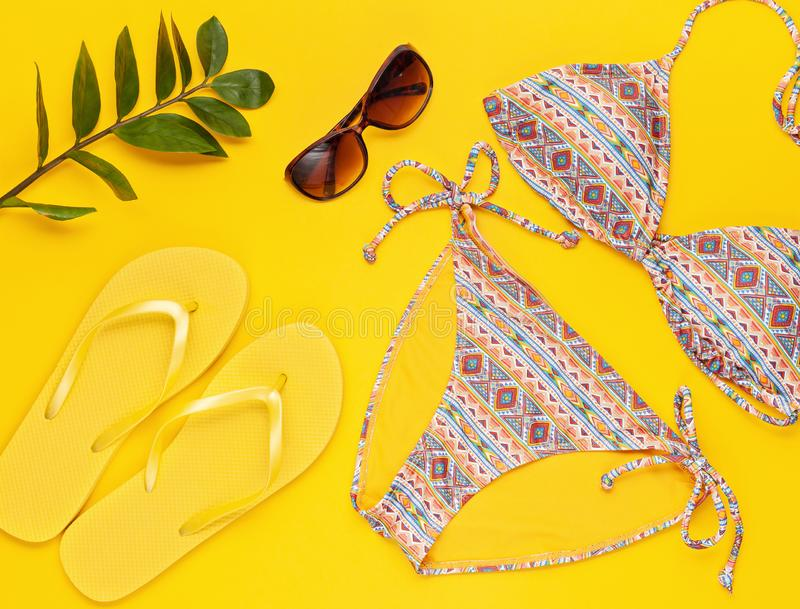 Summer vacation, travel, tourism concept flat lay. Tropical beach accessories top view with bikini, sunglasses and flip flops royalty free stock image