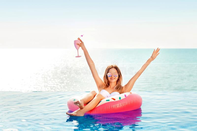 Summer Vacation. Woman in bikini on the inflatable donut mattress in the SPA swimming pool. Travel on the beach. Sea stock images