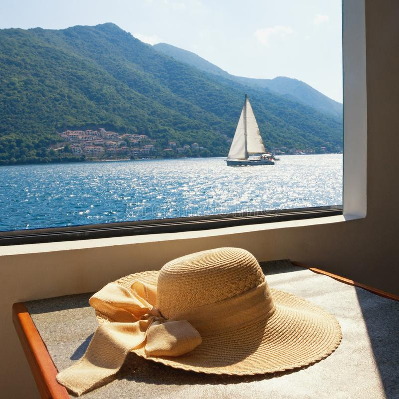 Summer vacation. Women`s sun hat on the table of pleasure ship royalty free stock photography