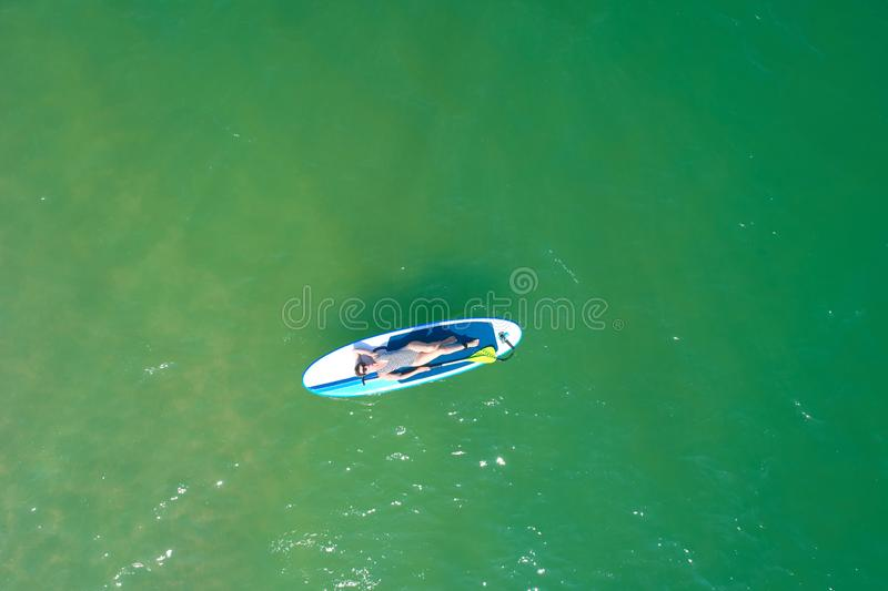 Summer Vacations. Beautiful Young Woman Relaxing on the SUP at Turquoise Water. Beauty, Wellness. Recreation. royalty free stock images