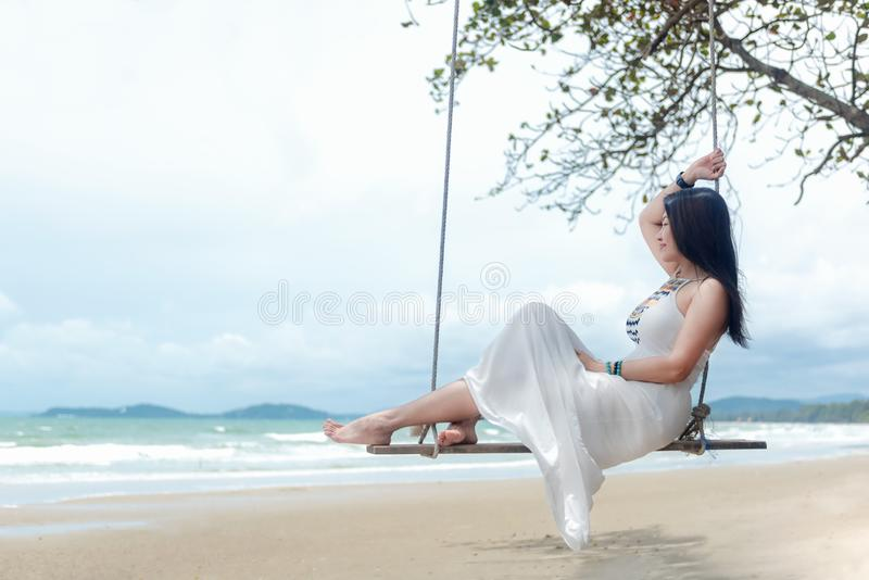 Summer Vacations. Lifestyle women relaxing and enjoying swing on the sand beach, fashion stunning women on the tropical island so stock photos