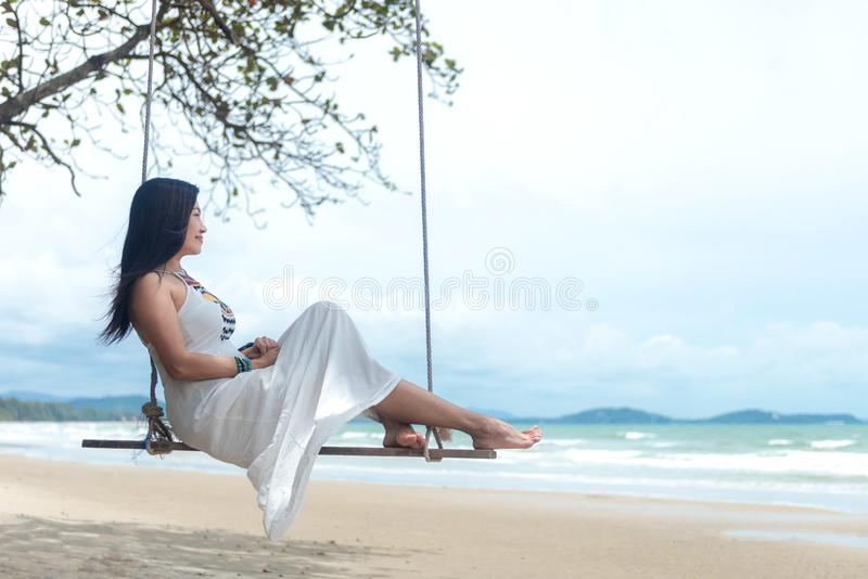 Summer Vacations. Lifestyle women relaxing and enjoying swing on the sand beach, fashion stunning women with white dress on the tr royalty free stock photography