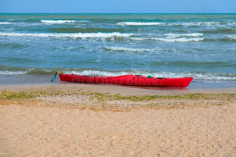 Summer Vacations. The red kayak is parked on the sandy beach on a sunny day, waiting for people to paddle out to sea. royalty free stock image