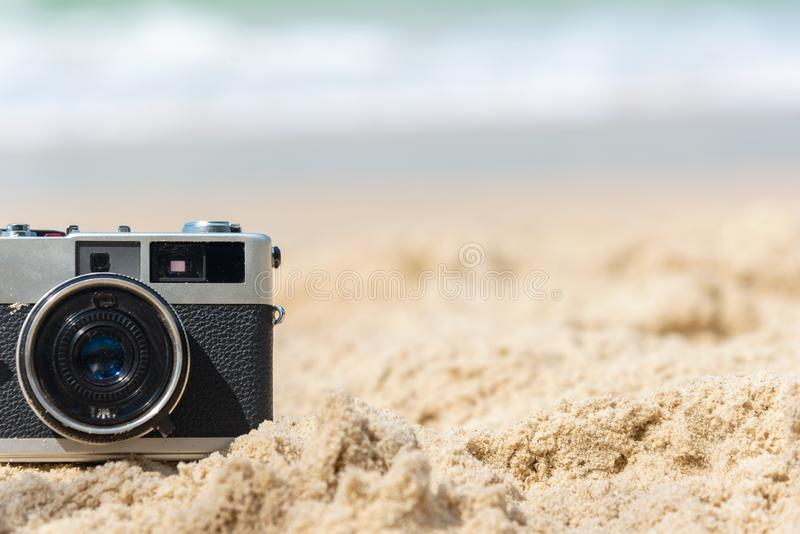 Summer Vacations. Vintage old camera of tourism on sandy beach. Travel concept background royalty free stock photo