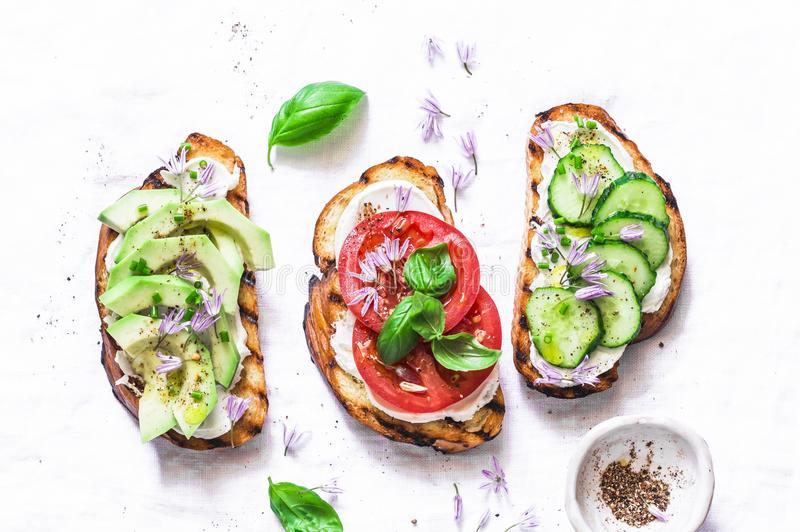 Summer variations of sandwiches - with cream cheese, avocado, tomato and cucumber on a light background, top view. Healthy diet fo stock photos