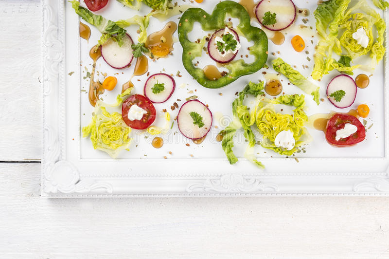 Summer vegetable salad on white tray. On wooden table, copy spacennframes,top view,border,corner royalty free stock photos