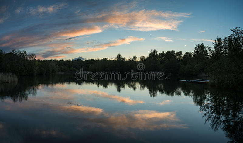 Summer vibrant sunset reflected in calm lake waters stock photo